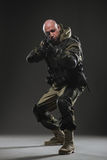 Metralhadora da posse do homem do soldado em um fundo escuro Imagem de Stock