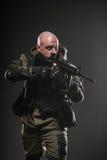 Metralhadora da posse do homem do soldado em um fundo escuro Foto de Stock Royalty Free