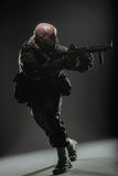 Metralhadora da posse do homem do soldado em um fundo escuro Imagens de Stock