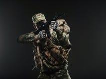 Metralhadora da posse do homem do soldado em um fundo escuro Fotos de Stock