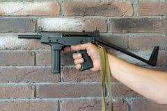 Metralhadora de PP-91 Kedr Um homem guarda uma metralhadora em sua mão no fundo de uma parede de tijolo marrom fotos de stock