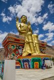 Golden statue of future Buddha on decorated podium, Likir, India stock photos