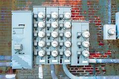 Metri elettrici e pannelli allegati al muro di mattoni Immagini Stock