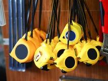 Metri gialli del nastro che appendono alla ferramenta per costruzione ed artigiani che lavorano nei campi differenti fotografia stock libera da diritti
