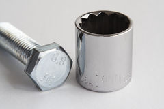 Metric Bolt and Socket. A grade 8.8 metric bolt lays on its side next to a chrome plated 19mm 12 point metric socket stock photos