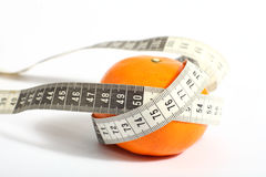 Metric tape measure and tangerine Royalty Free Stock Photo