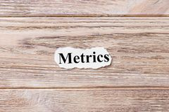 Metrics of the word on paper. concept. Words of Metrics on a wooden background.  Stock Images