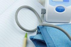 Metro automático del monitor de la presión arterial con el cuaderno vacío en blanco y una pluma Foto de archivo libre de regalías
