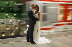 Metro Bride. Picture in metro station. just married couple stand on the metro station and just around the metro train passes. it shows the change of the life of royalty free stock photography
