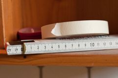 Metro de cinta de papel y de madera blanco en los estantes imágenes de archivo libres de regalías
