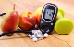 Metro de la glucosa con el estetoscopio, las frutas y las pesas de gimnasia médicos para usar en aptitud Fotografía de archivo libre de regalías