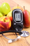 Metro del glucosio con lo stetoscopio medico, i frutti e le teste di legno per utilizzare nella forma fisica Immagini Stock Libere da Diritti