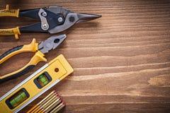 Metro di legno del livello della costruzione dei colpi di forbici della latta delle pinze sul bordo di legno Fotografie Stock