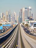 Metro Dubai. Parallel rails and typical city skyline of skyscrapers at the background, busy traffic road Royalty Free Stock Photography