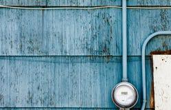 Metro elegante de la fuente de alimentación de la rejilla en la pared azul sucia Imágenes de archivo libres de regalías