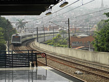 Metro in Medellin, Colombia. Metro station in city of Medellin of Colombia with oncoming train on the rails and houses at the the background stock images