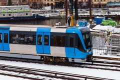 Metro moving on between stations and transporting people from work on a dy with snow stock images