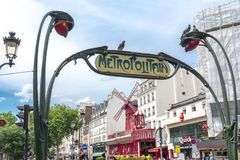 Metro sign and Moulin Rouge cabaret in Paris, France stock images