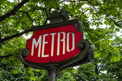 Metro sign in Paris. Red metro sign with green trees in the background stock photos