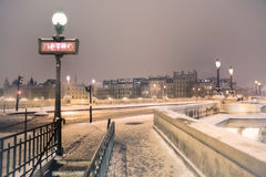 Metro sign under snow in Paris. Metro sign and entrance at the end of Pont Neuf in Paris, France, on a snowy winter night royalty free stock image