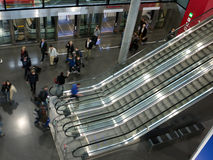 Metro station. A large metro station with the train in the station with open doors. People descending and  getting on the escalators Stock Photography