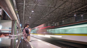 Metro station. Located in Shanghai, China, a subway station , Quiet girl waitingand speeding train Royalty Free Stock Photography