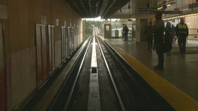 Metro station people standing on platform. Train leaving station commuters walking stock footage