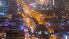 Metro station and traffic on the night road timelapse. Aerial view from the top of the building. Sheikh Zayed Road in Dubai and footbridge, skyscrapers on a stock video
