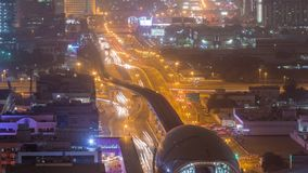 Metro station and traffic on the night road timelapse. Aerial view from the top of the building. Sheikh Zayed Road in Dubai and footbridge, skyscrapers on a stock footage