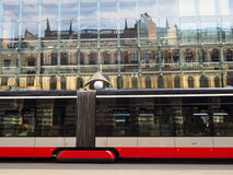 Metro Train Zooms Past Modern Building. A train speed through downtown Prague with reflection in modern building in the background Stock Images