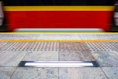 Metro vermelho borrado no Polônia de Varsóvia, pavimentação tátil para vi imagem de stock