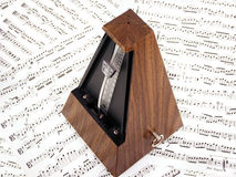 Metronome. A traditional wooden metronome sitting on sheet music Stock Photography