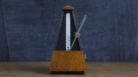 Metronome clicking on a table stock footage