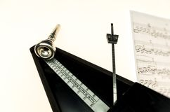 Metronome and mouthpiece of a trumpet isolated on a blank white Royalty Free Stock Photos
