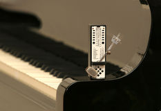 Metronome on a piano. Metronome standing on a piano royalty free stock image