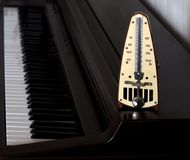 Metronome on piano keyboard. Background Stock Images
