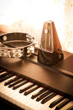 Metronome on a piano with tambourine. Royalty Free Stock Images