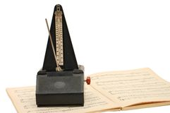 Metronome on sheet music. Background Stock Photos
