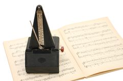 Metronome on sheet music. Background Royalty Free Stock Photos