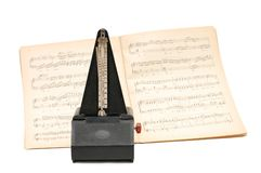 Metronome on sheet music background. Isolated Royalty Free Stock Images