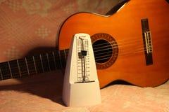 Metronomo con la chitarra classica Fotografia Stock