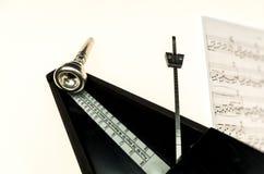 Metronoom en mondstuk van een trompet op een leeg wit wordt geïsoleerd dat Royalty-vrije Stock Foto's