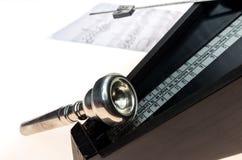 Metronoom en mondstuk van een trompet op een leeg wit wordt geïsoleerd dat Stock Afbeelding
