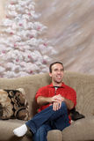 Metrosexual Christmas Man. A smiling metrosexual man sitting on a sofa in front of a hand painted christmas tree Royalty Free Stock Image