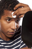 Metrosexual. Dark-skinned young man cleans his face with cotton pad stock photography
