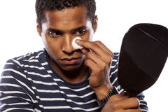 Metrosexual. Dark-skinned young man cleans his face with cotton pad royalty free stock image