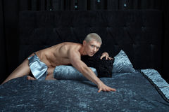 Metrosexual man on the bed. Royalty Free Stock Photo