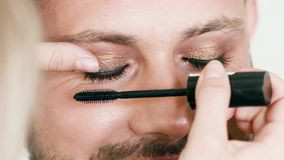 Metrosexual Man Or Gay Getting Eyelashes Painting. Closeup of unrecognizable makeup artist paints eyelashes of attractive metrosexual or gay man. Portrait of stock video