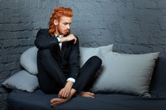 Metrosexual man sitting on the couch. Royalty Free Stock Photo