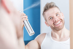 Metrosexual man using hair spray Royalty Free Stock Photo